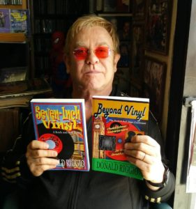 Elton John holds a Riggio oldies novel in each hand